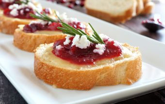 Holiday crostini appetizers with cranberry sauce brie feta and rosemary close up on a white plate